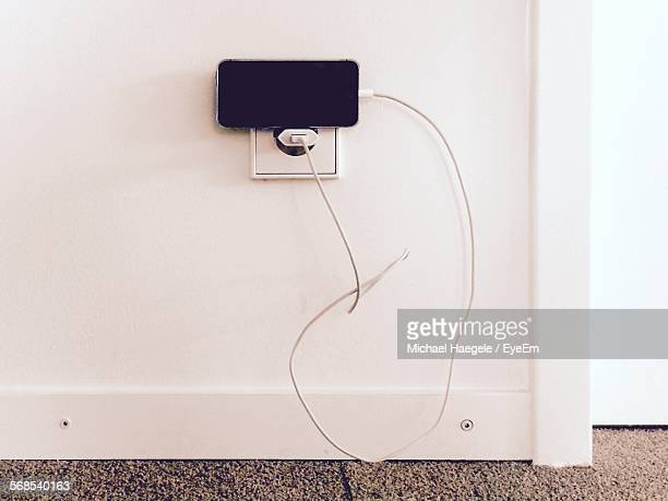 High Angle View Of Smart Phone Charging Against White Wall