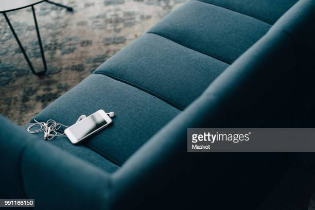 High angle view of smart phone on couch at office in conference