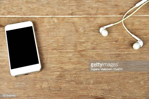 High Angle View Of Smart Phone With Earphones On Table