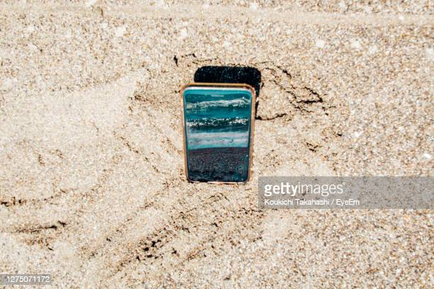 high angle view of smartphone reflected sea on the beach - koukichi stock pictures, royalty-free photos & images