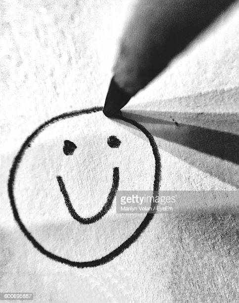 High Angle View Of Smiley Face Being Drawn On Paper