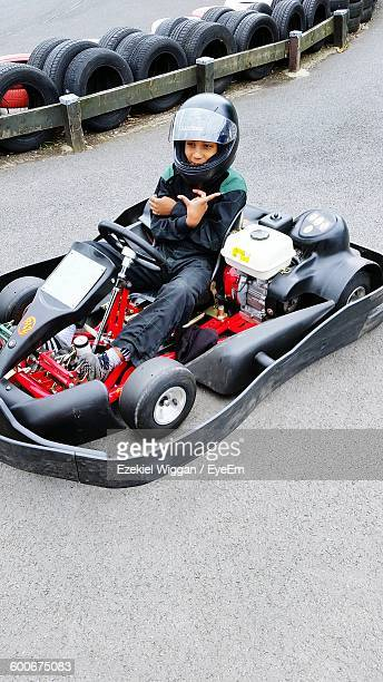 High Angle View Of Smiling Boy Sitting In Racecar