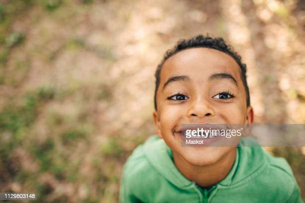 high angle view of smiling boy with gap toothed in park - personas sin dientes fotografías e imágenes de stock