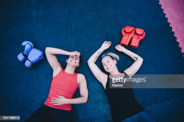 High angle view of smiling female athletes lying on floor at health club