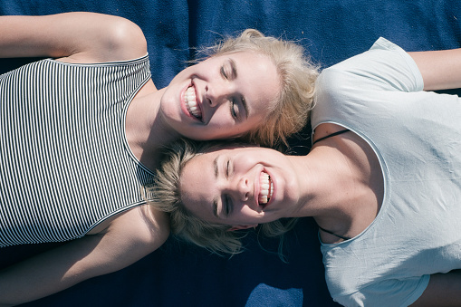 High Angle View Of Smiling Friends Lying On Bed - gettyimageskorea