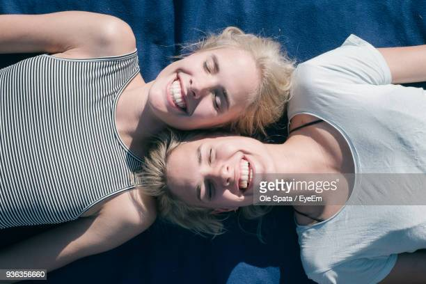 High Angle View Of Smiling Friends Lying On Bed