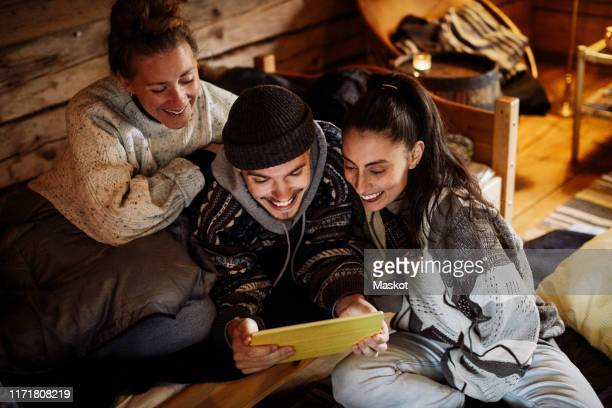 high angle view of smiling friends watching movie over digital tablet while relaxing in cottage - color out of space 2019 film stockfoto's en -beelden