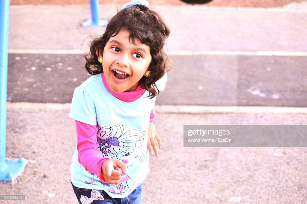 High Angle View Of Smiling Girl Pointing While Standing On Footpath : Stock Photo