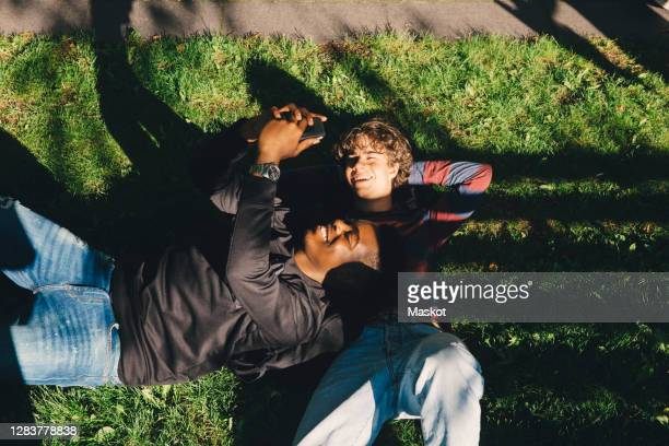 high angle view of smiling male friends taking selfie while lying on grass in park - lying down stock pictures, royalty-free photos & images