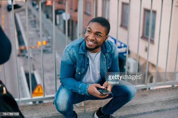 high angle view of smiling man crouching against railing while looking away on footbridge in city - footbridge stock photos and pictures
