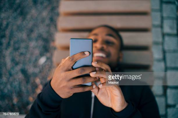 High angle view of smiling man using smart phone while lying on bench