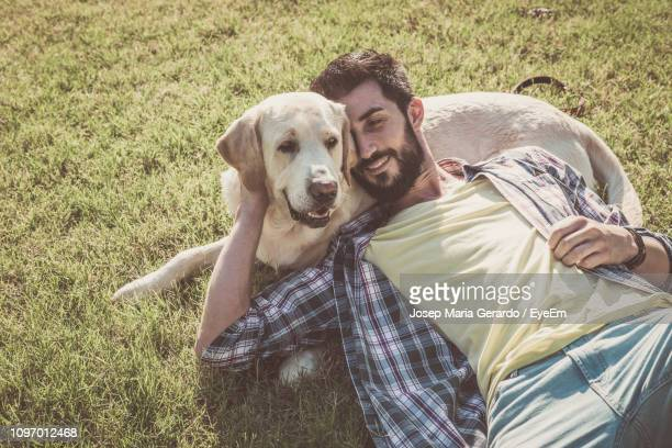high angle view of smiling mid adult man lying on dog at park - lying down stock pictures, royalty-free photos & images