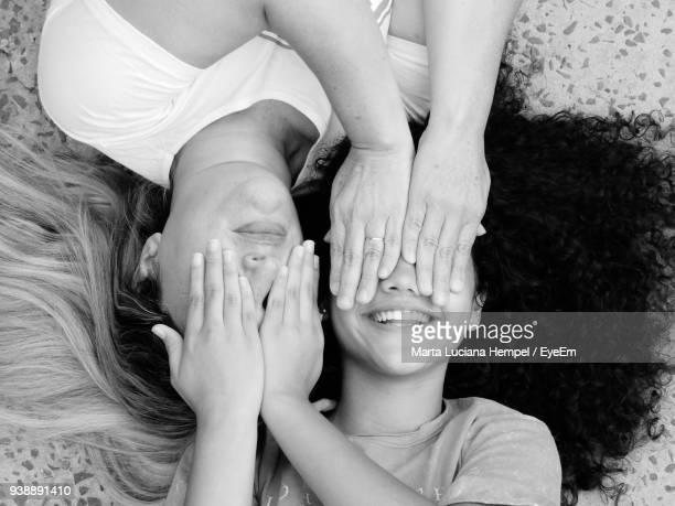 High Angle View Of Smiling Mother And Daughter Covering Eyes While Lying On Floor