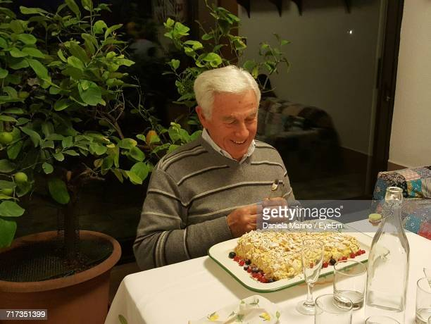 High Angle View Of Smiling Senior Man Sitting By Birthday Cake On Table