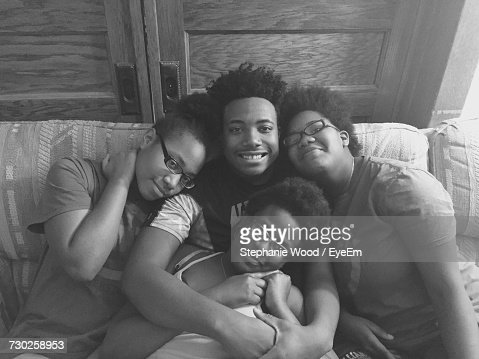 High Angle View Of Smiling Siblings Sitting On Sofa At Home