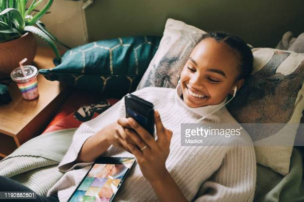 high angle view of smiling teenage girl listening music while using mobile phone on bed at home - one teenage girl only stock pictures, royalty-free photos & images