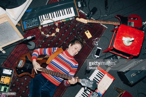 high angle view of smiling woman playing guitar while lying on carpet at studio - tambourine stock pictures, royalty-free photos & images
