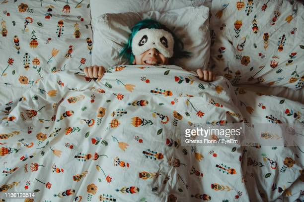 high angle view of smiling woman sleeping under blanket on bed at home - bettwäsche stock-fotos und bilder
