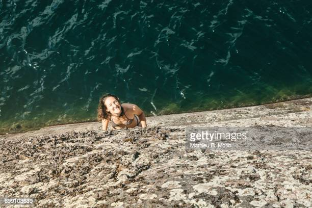 high angle view of smiling young woman looking up on a rock ledge - sudbury canada stock photos and pictures