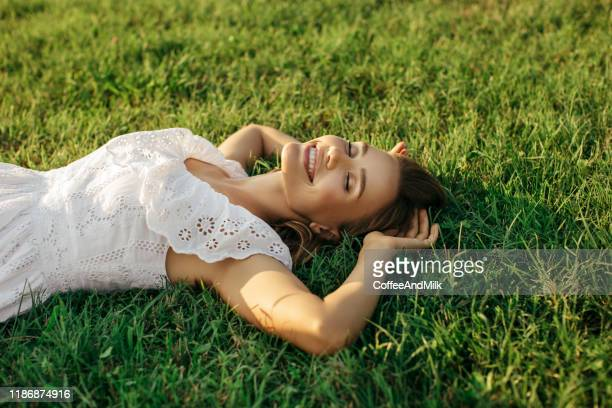 high angle view of smiling young woman lying down on grass - lying down stock-fotos und bilder