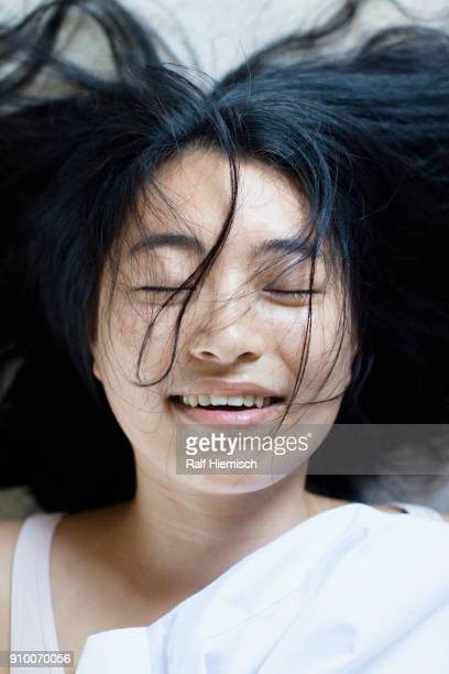High angle view of smiling young woman with closed eyes and messy hair lying on bed