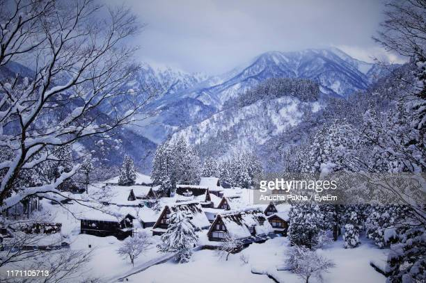 high angle view of snow covered houses and trees by mountains - 世界遺産 ストックフォトと画像