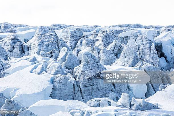high angle view of snow covered rock formations - crevasse stock photos and pictures