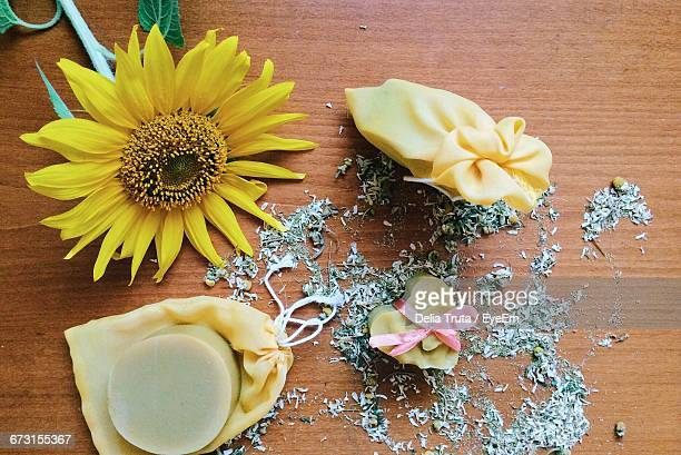 High Angle View Of Soaps By Sunflower On Wooden Table