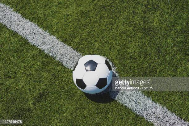 high angle view of soccer ball on field - palla sportiva foto e immagini stock