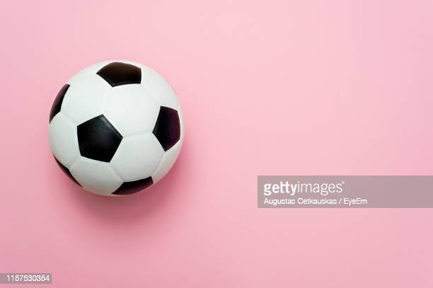 high angle view of soccer ball on pink background - spielball stock-fotos und bilder