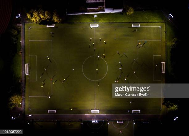 high angle view of soccer field at night - stadion stock-fotos und bilder
