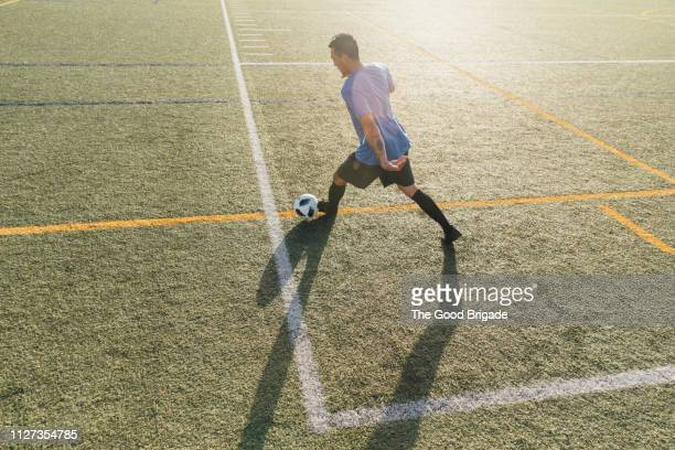 High angle view of soccer player kicking ball on field