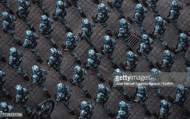 high angle view of soldiers walking on street - arrangement stock pictures, royalty-free photos & images