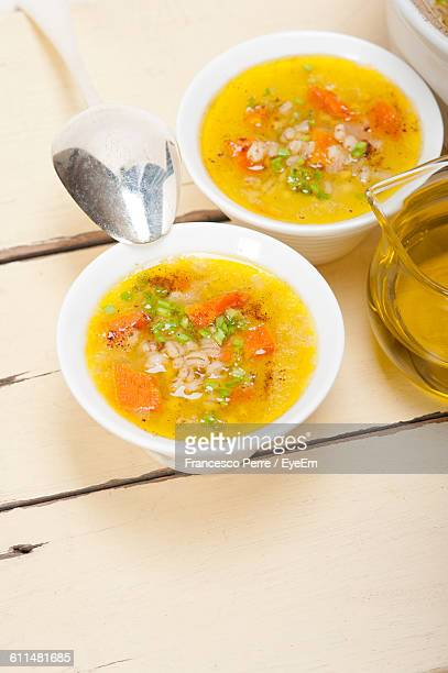 High Angle View Of Soup Served In Bowl By Oil Jar On Wooden Table