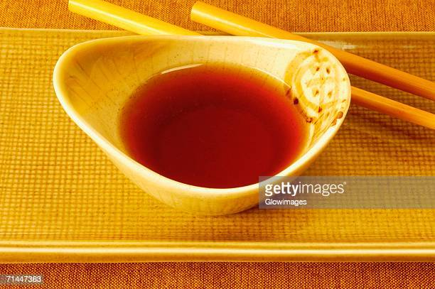 High angle view of soy sauce in a bowl with a pair of chopsticks
