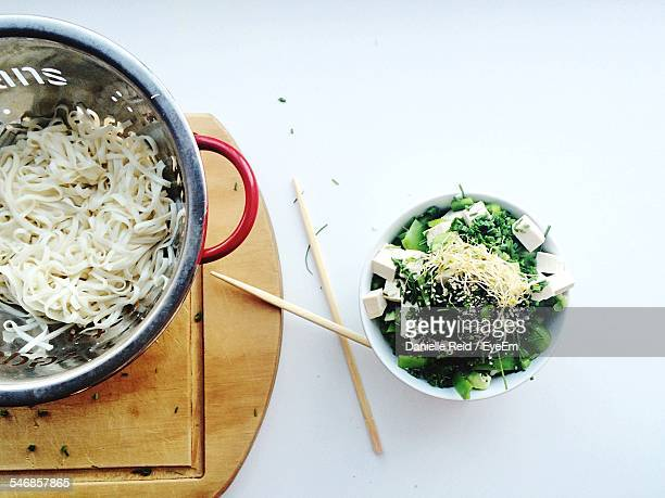 high angle view of spaghetti by coriander and cheese on bowl against white background - danielle reid stock pictures, royalty-free photos & images