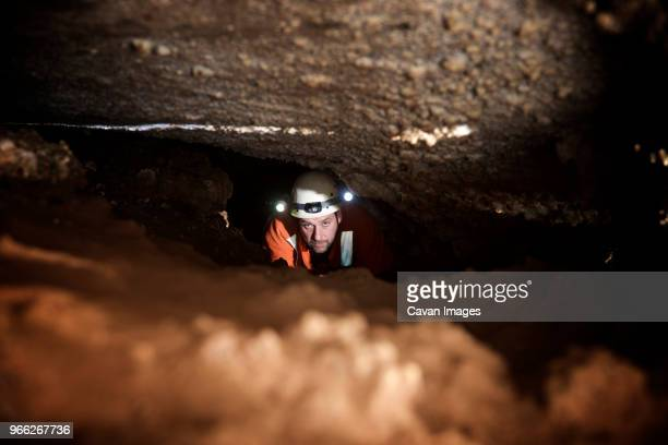 high angle view of spelunker standing in cave - spelunking stock pictures, royalty-free photos & images