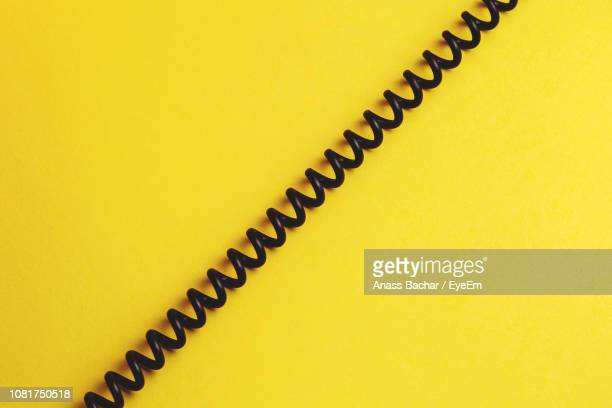 High Angle View Of Spiral Cable On Yellow Background