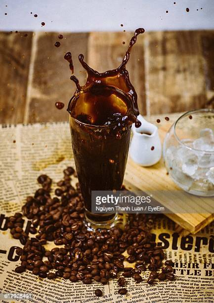 High Angle View Of Splashing Coffee With Roasted Coffee Beans On Table At Cafe