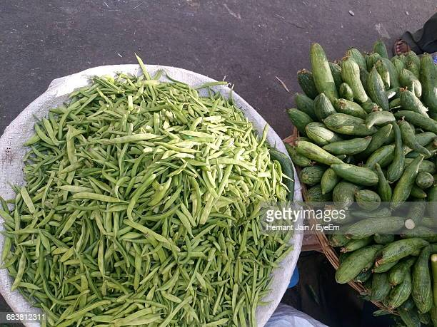 high angle view of sponge gourds and green beans for sale at street market - loofah stock photos and pictures