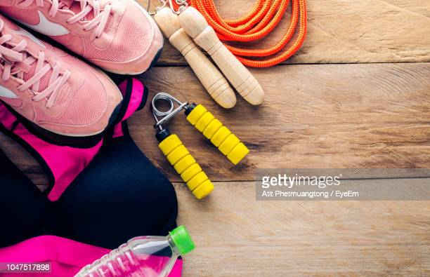 High Angle View Of Sports Clothing With Shoe And Equipment On Table