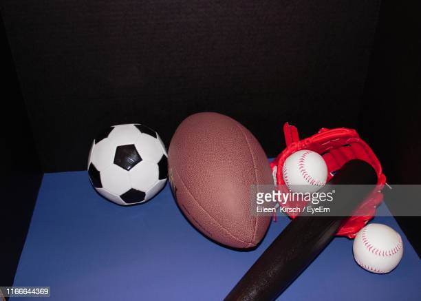 high angle view of sports equipment on table against black background - eileen kirsch stock pictures, royalty-free photos & images