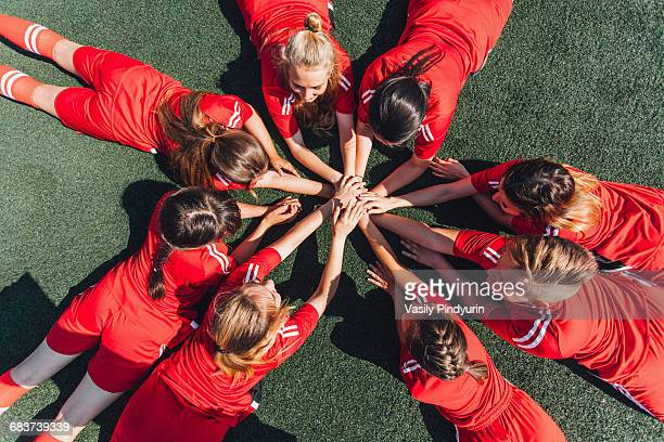 High angle view of sports team stacking hands on field