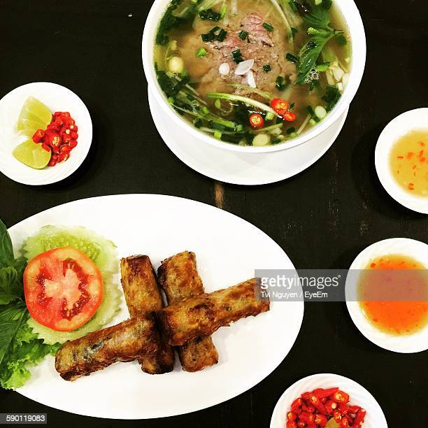 High Angle View Of Spring Rolls And Soup On Table