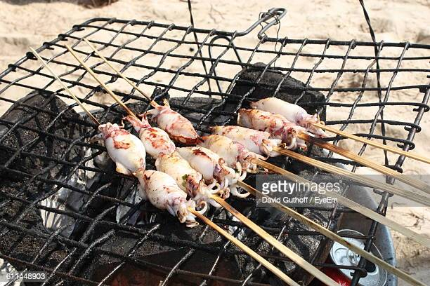 High Angle View Of Squids Being Grilled On Barbecue At Beach