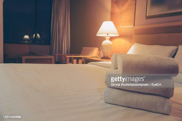 high angle view of stacked towel on bed at hotel - towel stock pictures, royalty-free photos & images