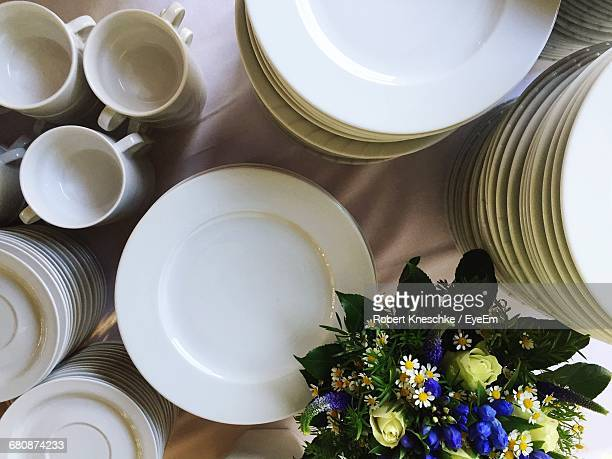 High Angle View Of Stacked White Plates And Cups On Table During Wedding