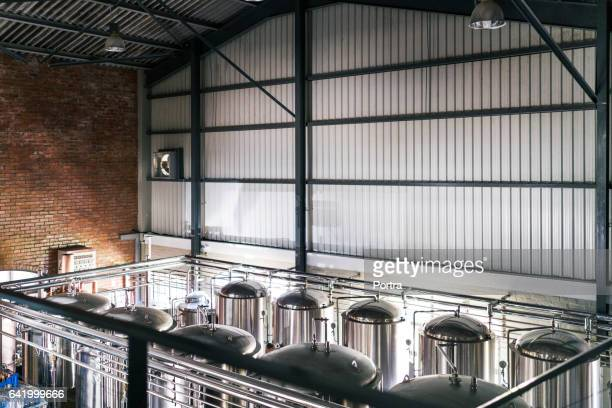 high angle view of steel vats in brewery - storage tank stock photos and pictures