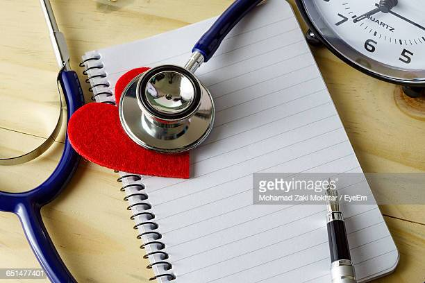 High Angle View Of Stethoscope And Heart Shape On Book