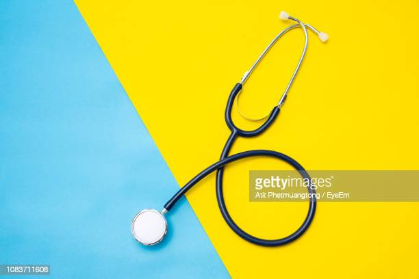 high angle view of stethoscope on colored background - stethoskop stock-fotos und bilder